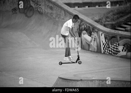 Tricks on a scooter in skateboard park - Stock Photo