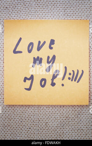 Adhesive note with Love my job text on a bulletin board - Stock Photo