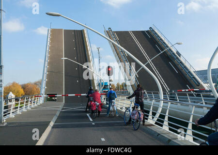 Cyclists wait as the Julianabrug Juliana Bridge opens to let a ship / barge / vessel pass underneath. Holland, The - Stock Photo