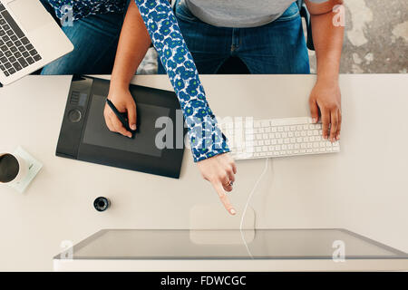 Top view cropped shot of a man using digital graphics tablet with stylus and computer keypad, with woman pointing at computer mo