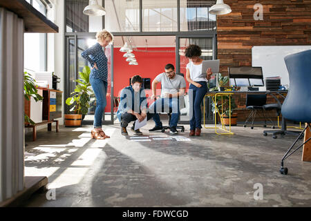 Mixed race group of creative people meeting in the office and discussing. Creative people looking at project plans - Stock Photo