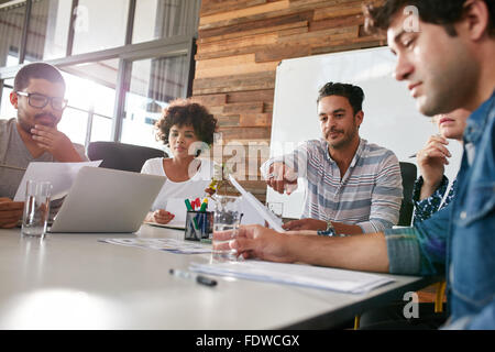 Multiracial group of business people meeting in modern office. Team holding business plan discussing about progress - Stock Photo