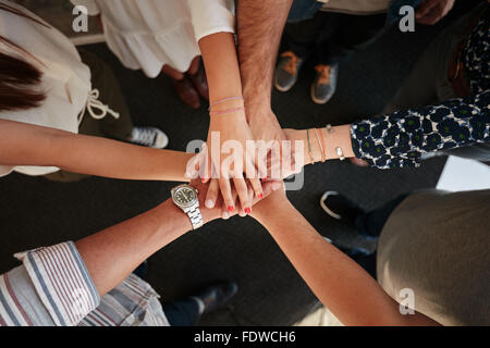 Top view of young creative professionals putting their hands together as a symbol of teamwork, cooperation and unity. - Stock Photo