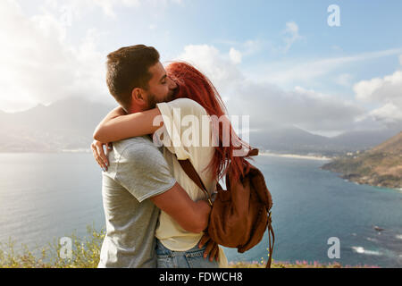 Portrait of a happy young couple enjoying a romantic embrace outdoors. Young man hugging his girlfriend while standing - Stock Photo
