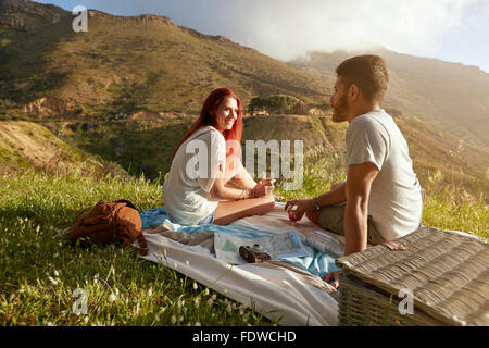 Young man and woman sitting on the grass during a picnic with glass of wine. Loving young couple having a conversation - Stock Photo