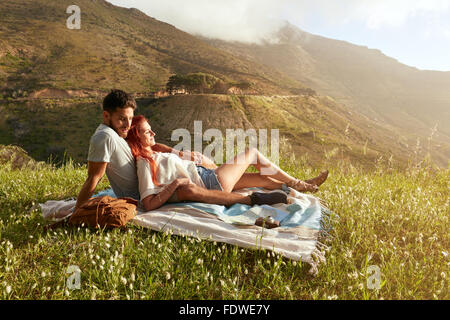 Happy young couple on picnic blanket. They are relaxing together on a summer day. - Stock Photo
