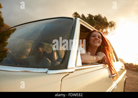 Portrait of happy young woman going on a road trip leaning out of window. Female enjoying travelling in a car with - Stock Photo