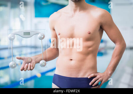 Fit man holding a weighting scale - Stock Photo