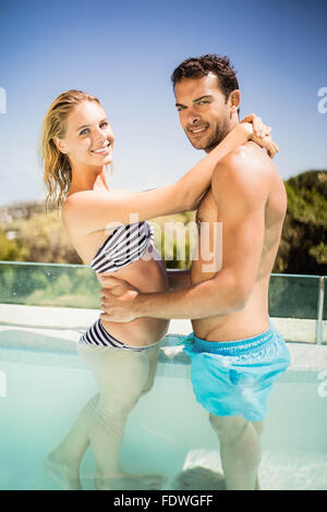 Happy couple embracing in the pool - Stock Photo
