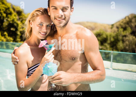 Happy couple holding cocktail - Stock Photo