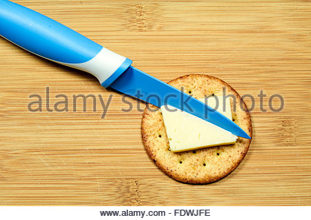 Savoury cheese biscuit on a wooden board with a blue handled knife - Stock Photo