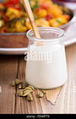 Yoghurt with cardamom in a small glass jar - Stock Photo