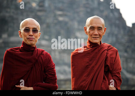 Portrait of two buddhist monks posing in front of  Borobudur Buddhist temple complex in Central Java, Indonesia - Stock Photo