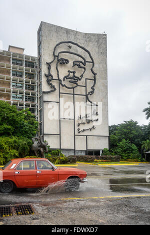 Cuban Lada car drives past the iconic artwork of Che Guevara in Revolution Square, Havana, Cuba on a wet day. - Stock Photo