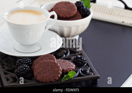 Chocolate cookies with coffee on black tray - Stock Photo