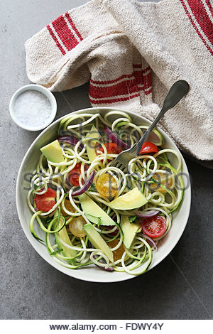 Zucchini noodles with cherry tomatoes,onion and avocado on a plate.Top view - Stock Photo