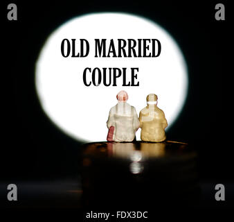 Miniature figurine pensioners sitting on coins in front of a spotlight showing the words Old married couple - Stock Photo