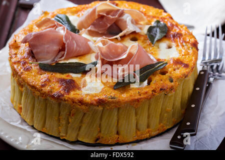 Pasta pie with cheese sauce, prosciutto and sage - Stock Photo