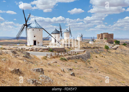White windmills on the hill near the castle in Consuegra, Toledo province, Spain - Stock Photo