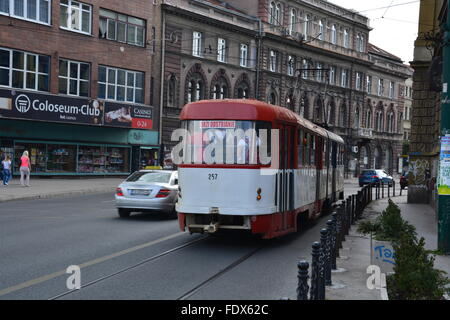 A red and white cable tram heads off on the streets of Sarajevo, Bosnia and Herzegovina. - Stock Photo