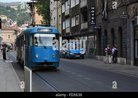 A blue cable tram goes down the street in Sarajevo, Bosnia and Herzegovina. - Stock Photo