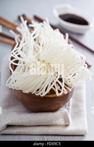 Dry raw rice noodle in a wooden bowl - Stock Photo