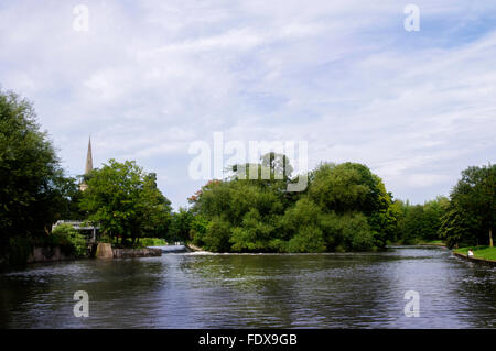 Looking across the water of the River Avon to Lucy's Mill Weir, Stratford upon Avon, with the spire of Holy Trinity - Stock Photo