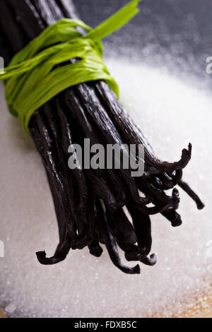 Sugar on a chalkboard and whole vanilla beans - Stock Photo