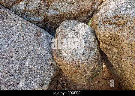 A stone wedged between two boulders in Hellhole Canyon, Anza-Borrego Desert State Park, California - Stock Photo