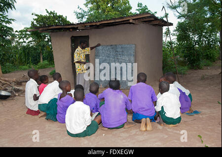 Children learning from a teacher at an outside classroom, Uganda. - Stock Photo