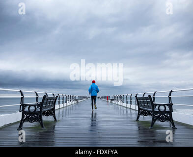 Mature man jogging on Saltburn pier in the rain. Saltburn by the sea. North Yorkshire. UK - Stock Photo