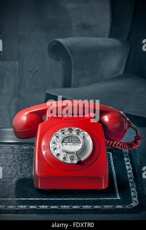 1960's red old retro dial telephone laquer 60's/70's GPO red BT phone on antique desk with atmospheric B&W toned - Stock Photo