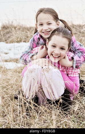 Two smiling sisters hugging in country field - Stock Photo