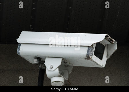 White worn out old surveillance camera with peeling paint and connected to black cable, mounted on bracket under - Stock Photo