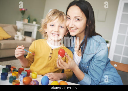Mother and son painting Easter eggs at home - Stock Photo