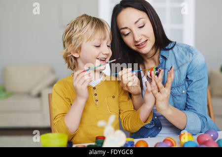 Young woman and her son painting Easter eggs - Stock Photo