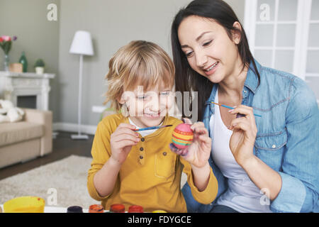 Mother and son painting Easter eggs before holiday - Stock Photo