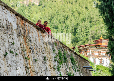 Two monks sit on a wall in Thimphu, Bhutan - Stock Photo