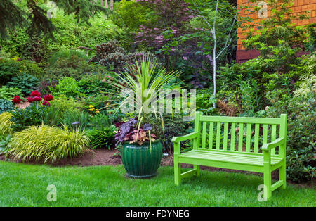 Vashon-Maury Island, WA: A chartreuse bench and green pot of heuchera (Heucherella sp) and palm in a perennial garden - Stock Photo