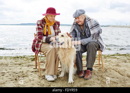 Elderly couple with Labrador sitting on the beach - Stock Photo