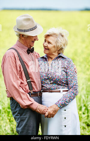 Amorous seniors looking at one another in blooming meadow - Stock Photo