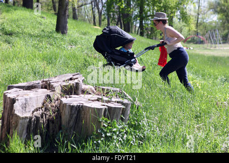 Berlin, Germany, woman pushing her child in a stroller up hill - Stock Photo