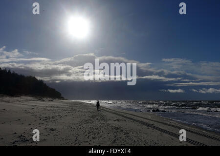 Kolberg, Poland, Woman runs with sunshine alone along the beach - Stock Photo