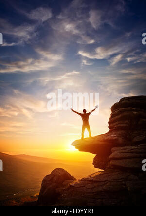 A person reaching up from a high point, set against a sunset. Expressing freedom - Stock Photo