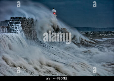 Large waves collide into the sea wall as storm hits  Lighthouse, Porthcawl.  Bridgend, South Wales, UK - Stock Photo