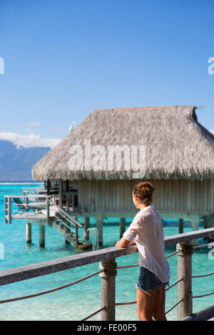 Woman on jetty of overwater bungalows of Sofitel Hotel, Moorea, Society Islands, French Polynesia - Stock Photo