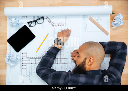 Young baldheaded african american young male designer with beard lying and sleeping on table with blueprint - Stock Photo