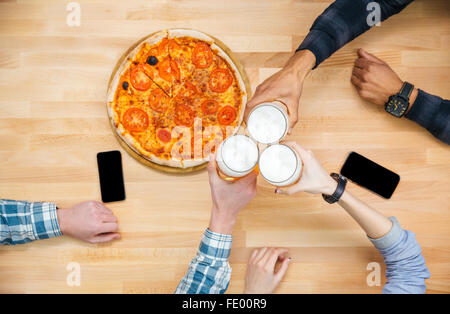 Top view of group of friends eating pizza and drinking beer - Stock Photo