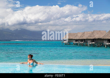 Woman in pool at Sofitel Hotel, Moorea, Society Islands, French Polynesia - Stock Photo