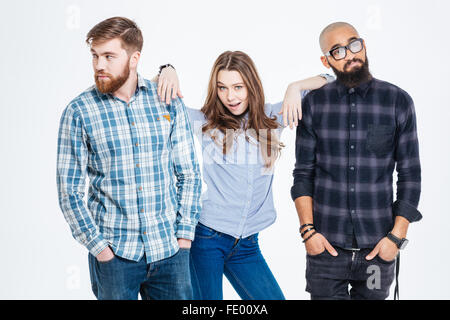 Beautiful confident young woman standing between two bearded pensive young men - Stock Photo